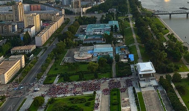 Bestudering van de panoramafoto's van Aram Pan kan verrassende situaties onthullen. Hier maken rond honderd mensen, in een straat onder de Juche-toren, zich klaar voor een gezamenlijke manifestatie. Geen idee wat er gebeurt. (Panoramafoto Pyongyang, Aram Pan)