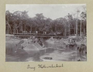 Een foto van de bouw van een spoorbrug over een kreek in het Surinaamse binnenland.