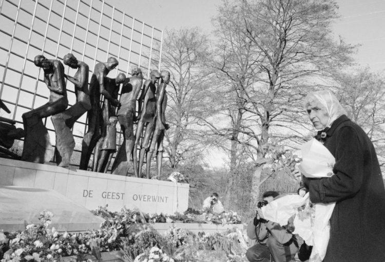 Vrouw met bloemen in de hand staat voor het monument. Stille bloemlegging voor slachtoffers uit de Tweede Wereldoorlog bij het Indisch Monument in Den Haag naar aanleiding van het overlijden van Keizer Hirohito van Japan. (cc - Erfgoed in Beeld)