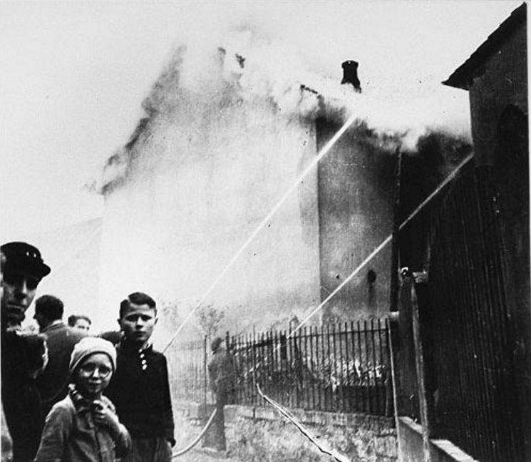 Terwijl de synagoge in Ober-Ramstadt op de ochtend na de Kristallnacht in de brand staat, kijken omwonenden toe. Brandweermensen voorkomen dat het vuur overslaat naar naburige panden.  (Bron: U.S. Holocaust Memorial Museum)