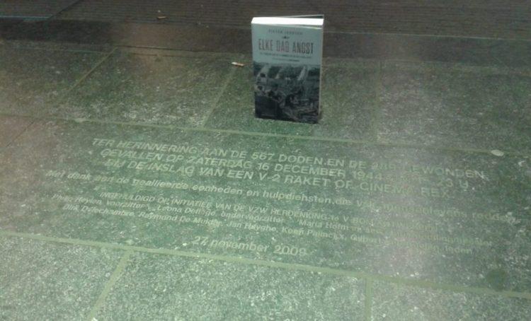 Herdenkingstegel aan de UGC, met daarbij het boek van Pieter Serrien