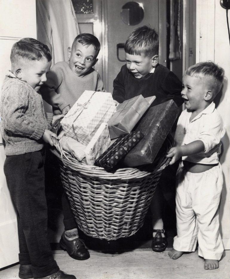 Sinterklaas: vier kinderen met grote rieten mand vol sinterklaaskadootjes. (Spaarnestad  - Walter Blum)