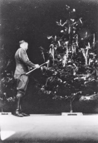 SS-officier Karl Hoecker steekt in Auschwitz kaarsjes aan in de kerstboom, slechts drie weken voor de bevrijding van het kamp. (USHMM)