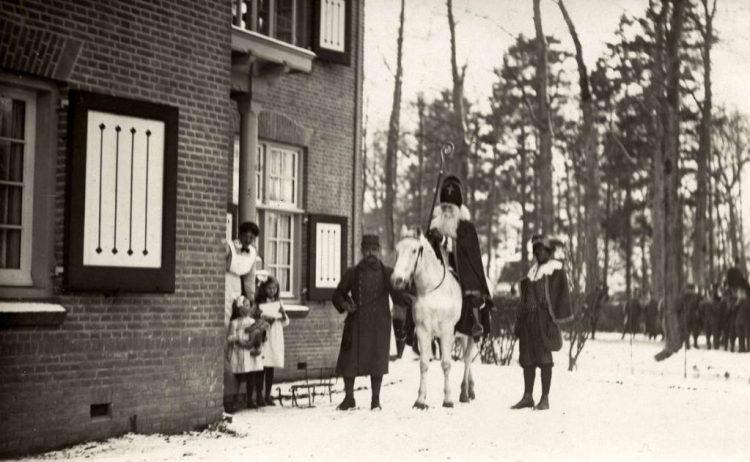 Folkore, Sinterklaasfeest. Intocht Sint Nicolaas in Loenen aan de Vecht. Foto: Sinterklaas te paard en Zwarte Piet brengen kinderen geschenken, in de sneeuw. Nederland, 1917. (GVNL - Fotocollectie Het Leven)