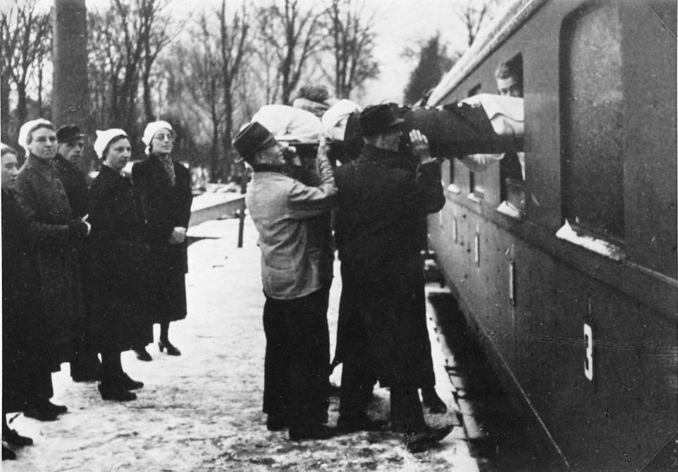 Een bedlegerige evacuée uit een ziekenhuis bij Santpoort wordt met op een brancard in de trein getild.