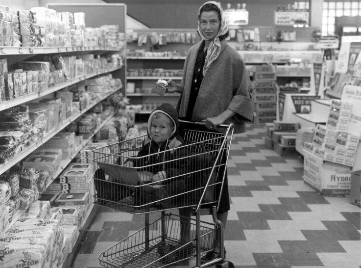 Huisvrouw met hoofddoek om, met haar zoontje in winkelwagen, doet boodschappen in de supermarkt. (Nationaal Archief - wiki)