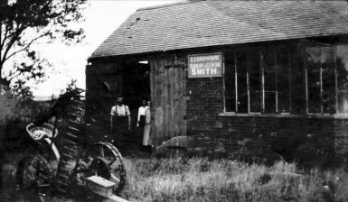 Charlie Browning, his wife Laura and their daughter Ivy outside the Smithy. 1920s. 'CJ Browning Shoeing & General Smith'