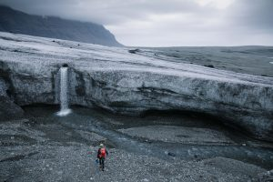 scientist standing in front of a glacier