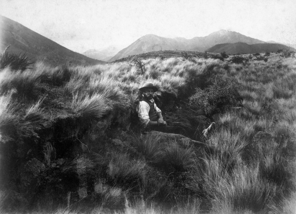 Black and white photo of Alexander McKay's son William on Glyn Wye station in 1888. McKay is sitting on the ground, using his body to indicate the size of the vertical rupture. It's the length of his legs, about 1 metre