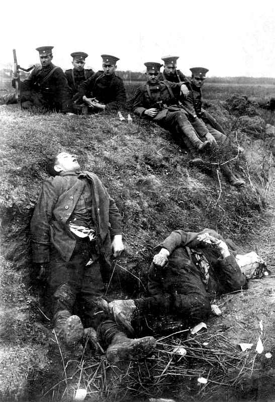 Members of the German Reichswehr sent to put down the Ruhr Uprising pose next to dead resistance fighters in Möllen, near Duisburg, 1920