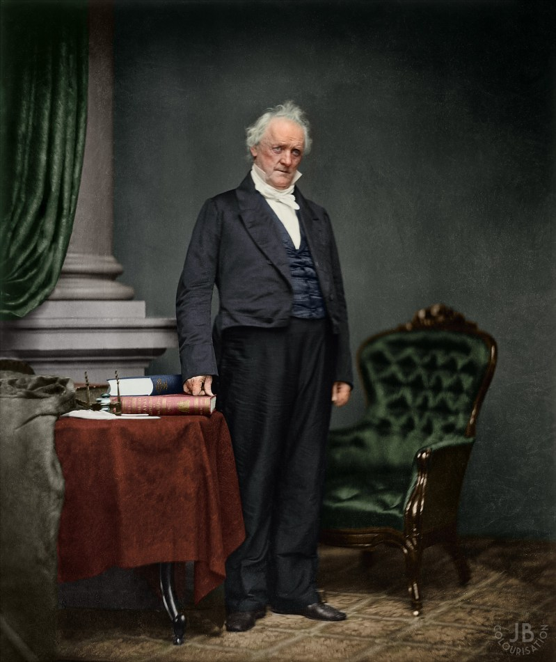 President James Buchanan in color. He is standing between a chair and a table that has books on it.