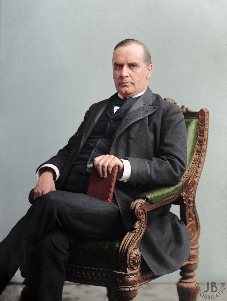 President William McKinley sitting on a chair with a book in his hand. The photo is in color.
