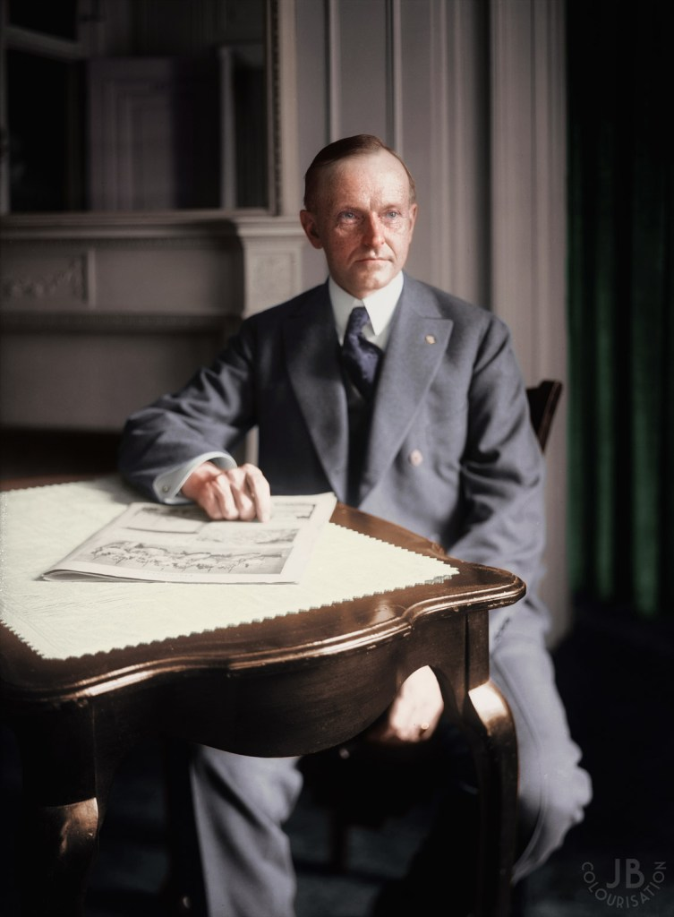 Calvin Coolidge sitting at a table with a suit on and a fireplace in the background. Color has been added to the photo through the process of colorization.
