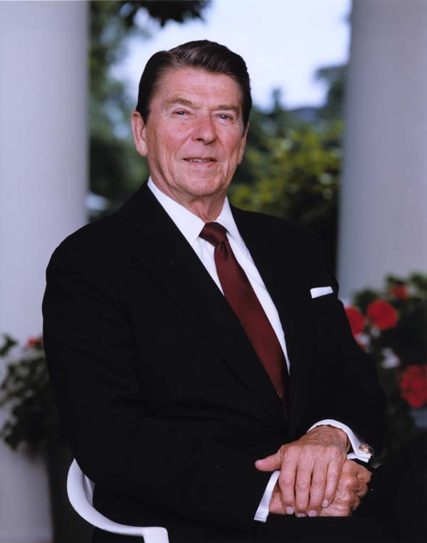 Ronald Reagan posing for a photograph outside with flowers behind him
