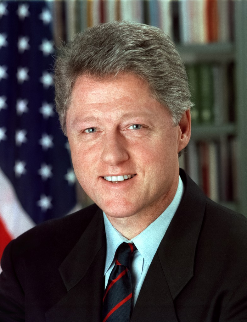 headshot of President Bill Clinton looking at the camera and smiling.