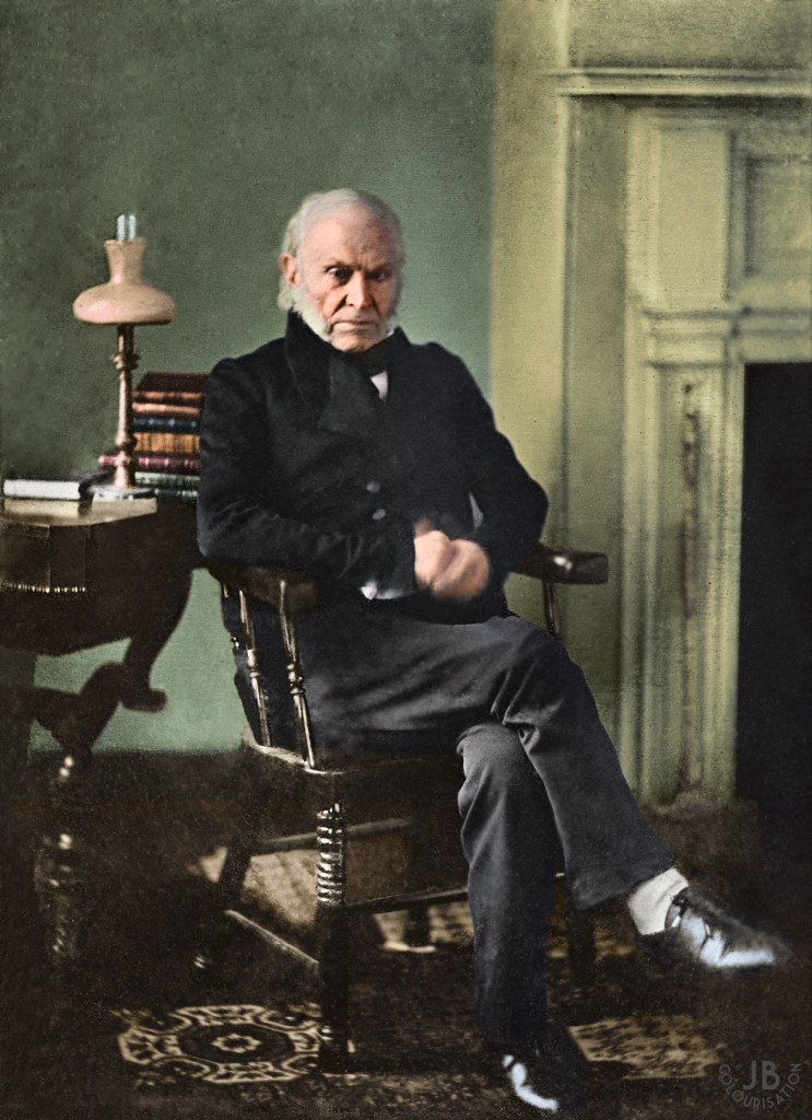 President John Quincy Adams having his portrait taken in a study with a table, lamp and books behind him. Adams is sitting on a chair holding his hand and a fireplace is to the right of him