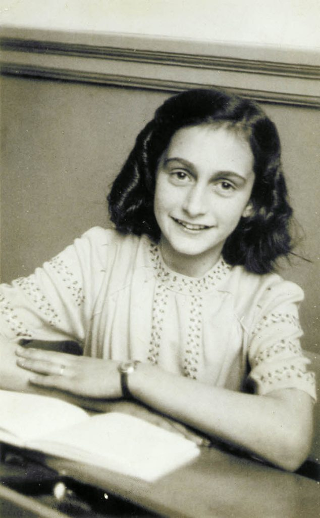 Anne Frank with her arms crossed and a book on the table smiling.