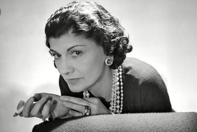 Coco Chanel with a cigarette in her hand looking at the camera.