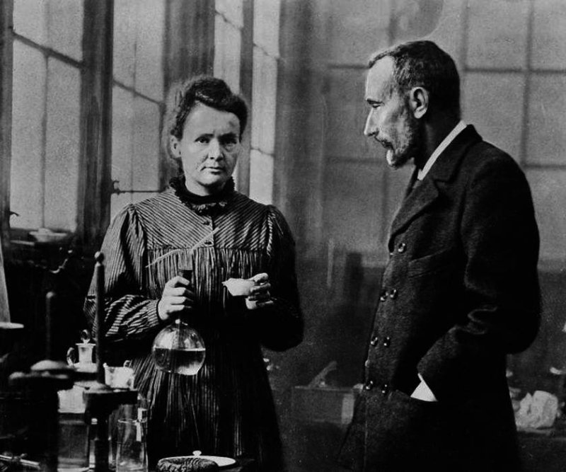 Marie Curie with a flask in her hand looking at the camera with her husband Pierre Curie.