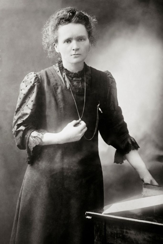 Marie Curie standing with her arm on a table in 1898