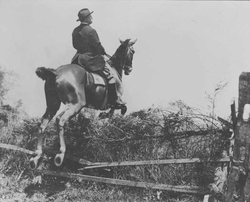 Theodore Roosevelt on a horse jumping over a broken down fence.