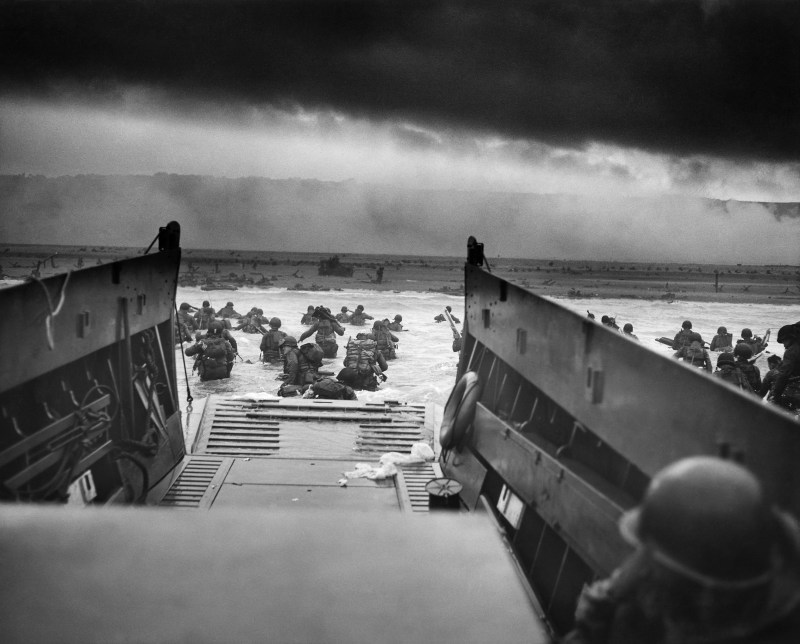 Soldiers jumping off of their boat and marching towards Omaha Beach on D-Day during the Second World War