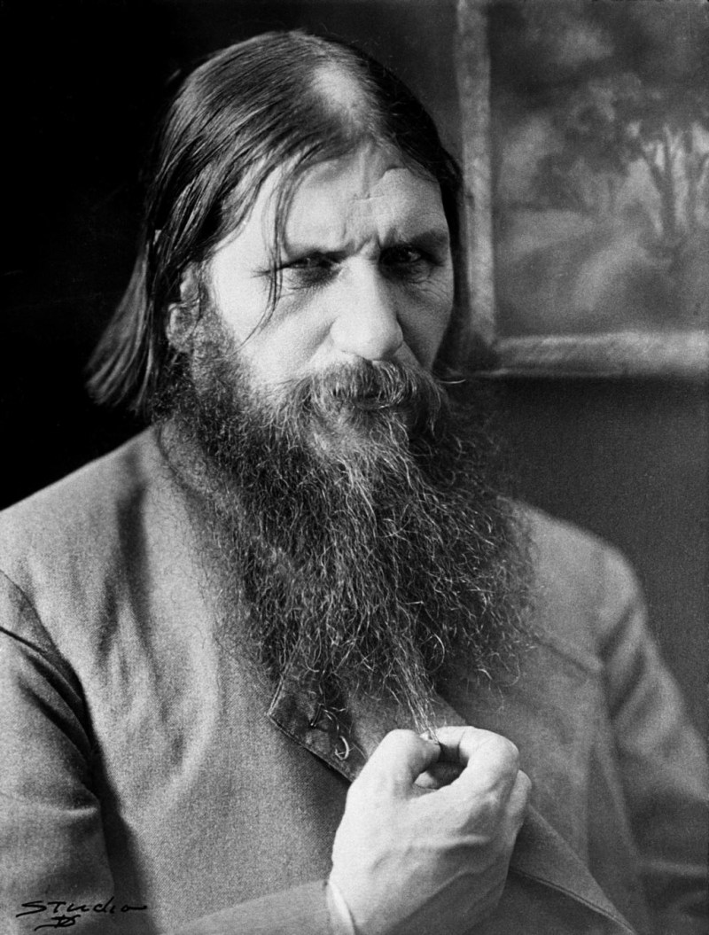 Rasputin in 1916 playing with his beard