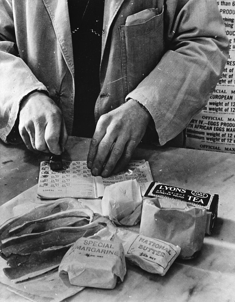 A shopkeeper is cancelling a ration book during World War 2.
