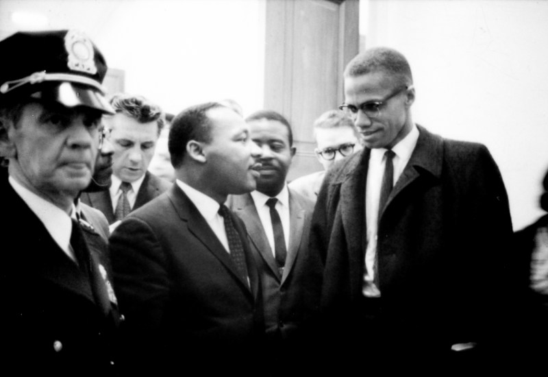 Martin Luther King and Malcolm X look at each other while waiting for a Press conference in Washington D.C. They are surrounded by people including a police officer looking away from them. 26 March 1964.