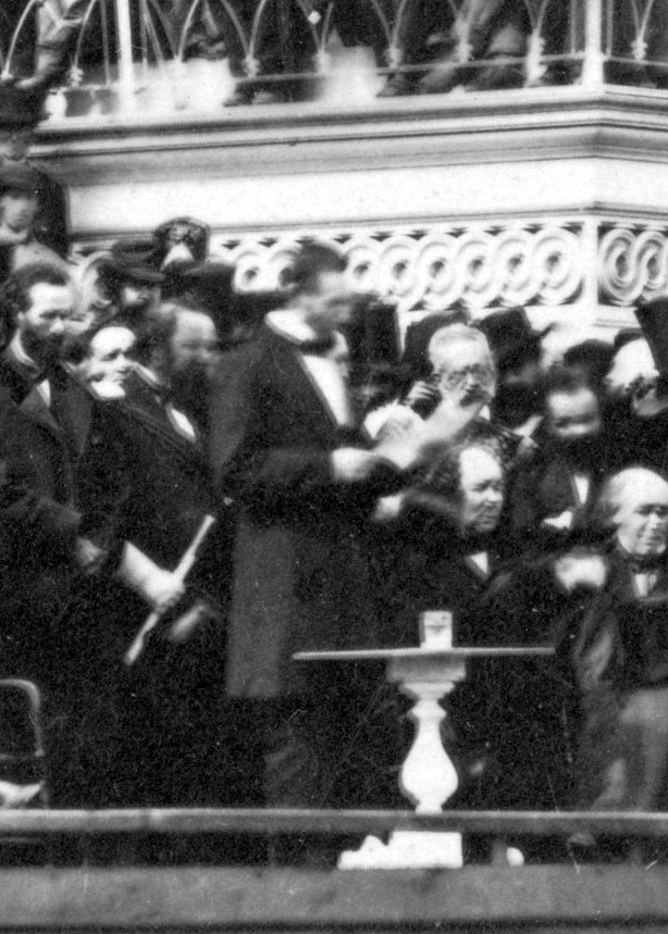 Abraham Lincoln in a suit with paper in his hand delivering his second inaugural speech.