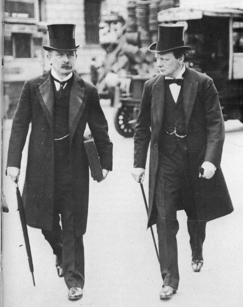 Winston Churchill and David Lloyd George both walking together wearing suits and top hats. Lloyd George is carrying a box and an umbrella, and Churchill is walking with a cane. 1907