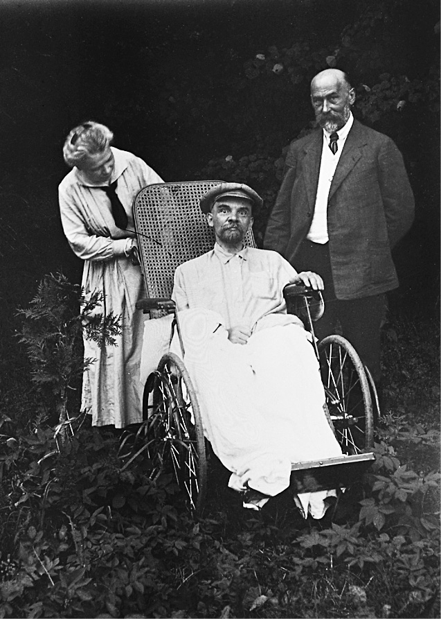 Vladimir Lenin wearing a hat and sitting in a wheelchair surrounded by greenery. His wife and doctor is standing near him. May 1923