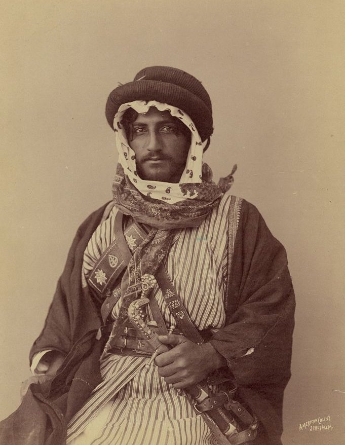 A historical photo of a bedouin warror in 1900. he is holding a weapon and wearing traditional clothing
