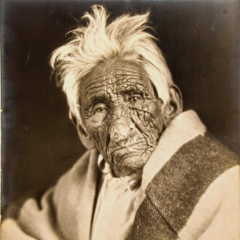 Chief John Smith with white hair and heavily wrinkled skin sitting for a photo with a blanket around him in circa 1915