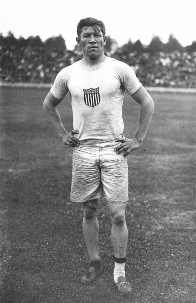 Jim Thorpe pictured in shorts, odd socks and his hands on his waist at the 1912 Olympics.