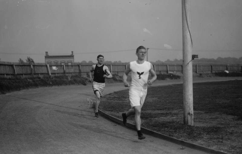 Jim Thorpe running on a track with another man named McGloughlin in Celtic park new york. Thorpe is wearing white shorts and a black vest with a C on it.