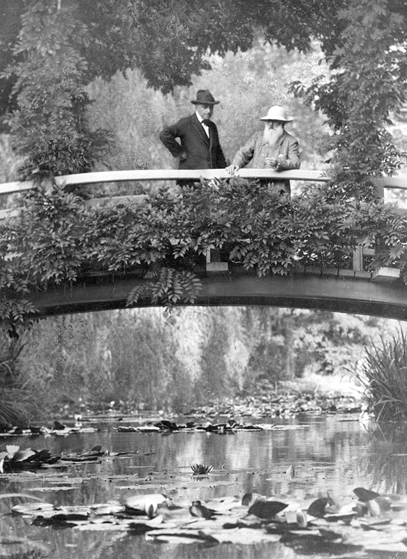 Photo of Monet standing on a bridge in his garden while showing a visitor around in 1922