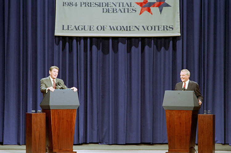 Ronald Reagan behind a podium debating Walter Mondale also behind a podium at the second presidential debate.