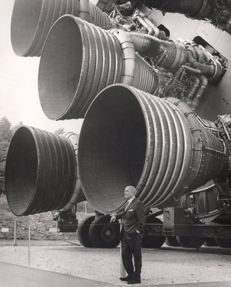 Aerospace engineer Wernher von Braun standing next to five F-1 rocket engines in 1969.