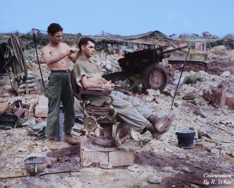 Colorized photograph of Pvt. Troy Dixon (standing) and Sgt. John Anderson (seated), Members of the 363rd Field Artillery Battalion, using a Japanese barber chair to cut hair on 10 June 1945 near Shuri, Okinawa.