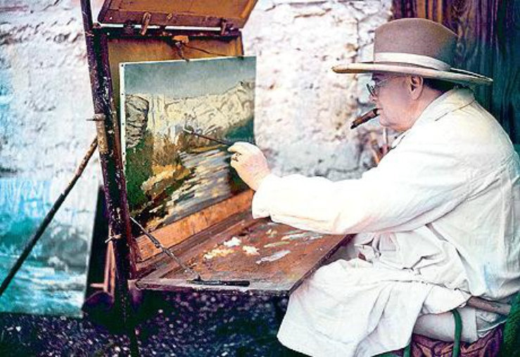 Winston Churchill seated wearing a jacket and large hat, painting a landscape in Southern France in 1955.