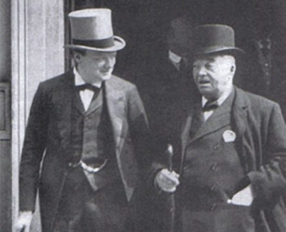 Winston Churchill in a suit and top hat standing on the left of the photo with Lord Jacky Fisher who is also wearing a suit. He has a cane and hat with him. They are standing outside of a building probably in London in 1913.