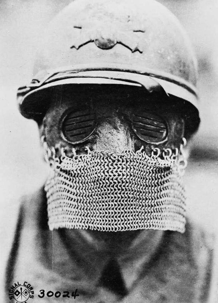black and white photograph of a french tank gunner during world war i wearing a chainmail splatter mask