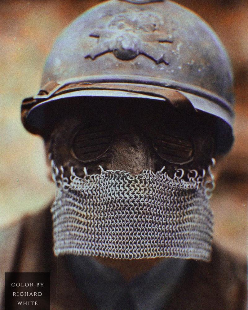 Color photograph of a French soldier wearing a WWI tank chainmail splatter mask