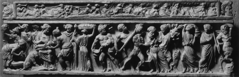 """This sarcophagus, also called the """"Childhood Sarcophagus,"""" depicts the birth of the god Dionysus (the Roman Bacchus) in exquisitely detailed high relief. At the left, the newborn god is nursed by a nymph and surrounded by Silenus-his future teacher-and other attendants, including one preparing a basin for the child's first bath. A panther cub, the god's favorite animal, is seated on the ground. To the right, satyrs and maenads, including a drunken old man, celebrate the god's birth. On the lid, satyrs and maenads-followers of the wine god-feast at a banquet. On the sides of the lid, Dionysus's panther drinks from an overturned wine vessel. The coffin is small, as if made for a child rather than for an adult."""
