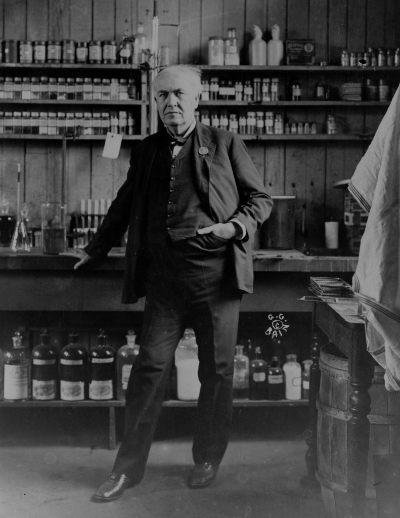 Thomas Edison standing in his lab with his arm on the table and his other hand in his pocket. Taken in 1911.