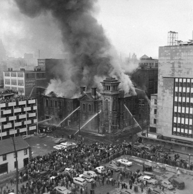 Just as it had started to become clear in Toronto, a combination of the NCC's abilities and mounting development pressures made the future of downtown surface lots a little hazier. In this photo, onlookers watch the Dominion Church burn from a City Parking lot in 1960. Image: Ted Grant / LAC Series 60-1181, Photo 33.