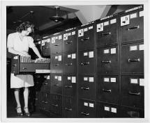 """Jeannette Poirier looking at photographs in file cabinet drawer at the Washington office of the Overseas Branch of the U.S. Office of War information."" 1945. Farm Security Administration – Office of War Information Photograph Collection, Library of Congress, https://www.loc.gov/pictures/item/2017758769."