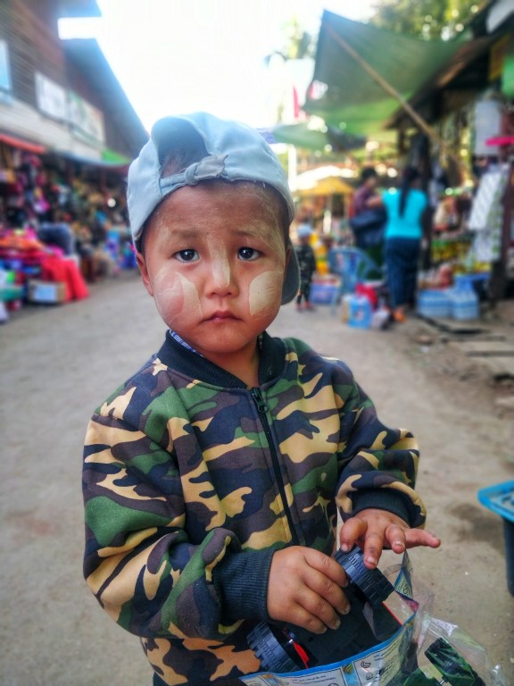 A young boy with Tanakha smeared on his cheeks – Tanakha is a yellowish-white organic paste used by all in Burma as a natural sunblock