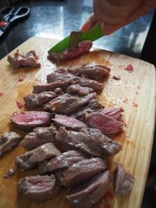 Jetzt noch das Fleisch mit einem scharfen Messer in kleine Stücke schneiden. Fertig sind die Chilaquiles.